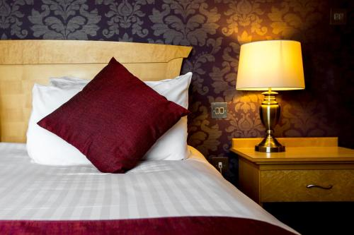 A bed or beds in a room at Hellidon Lakes Hotel