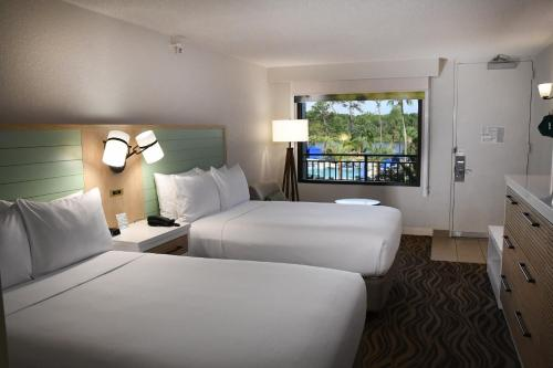 A bed or beds in a room at Wyndham Garden Lake Buena Vista Disney Springs® Resort Area