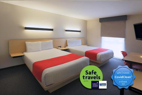 A bed or beds in a room at City Express Tijuana Insurgentes