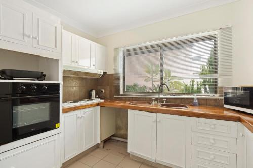 A kitchen or kitchenette at Location! 2BR Town View Unit in Centre of Airlie.