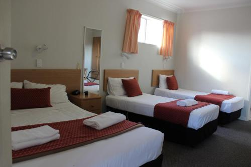 A bed or beds in a room at The Hume Inn Motel