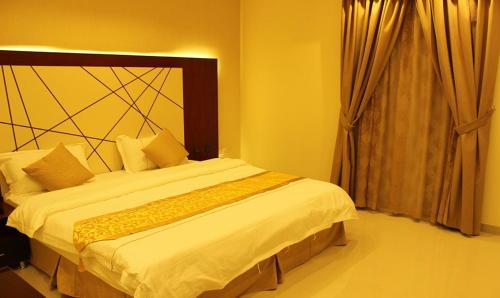 A bed or beds in a room at Abat Suites