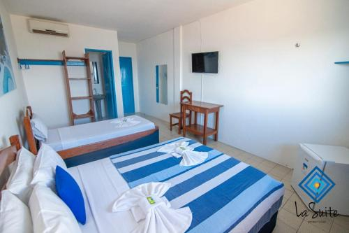 A bed or beds in a room at La Suite Praia Hotel