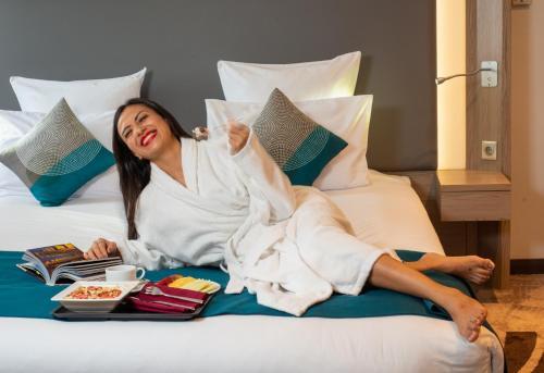 سرير أو أسرّة في غرفة في نوفوتيل المطار القاهرة