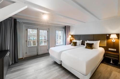 A bed or beds in a room at NH Collection Barbizon Palace Apartments