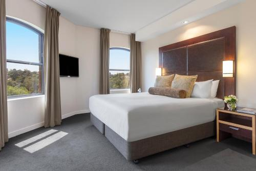 A bed or beds in a room at Amora Hotel Riverwalk
