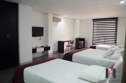 A bed or beds in a room at Hotel Merlott 70
