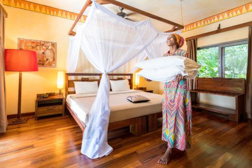 A bed or beds in a room at Zanzi Resort