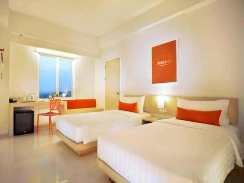 A bed or beds in a room at Zuri Express Lippo Cikarang