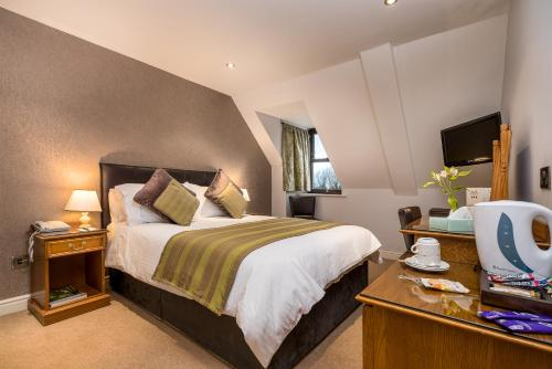 A bed or beds in a room at Le Friquet Hotel