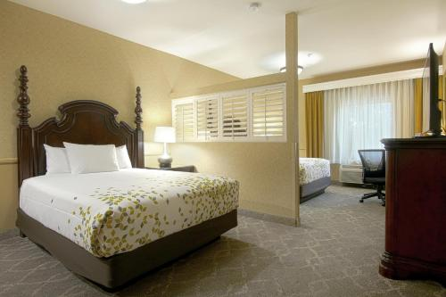A bed or beds in a room at Azure Hotel&Suites Ontario Trademark Collection by Wyndham