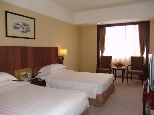 A bed or beds in a room at Guangyong Lido Hotel