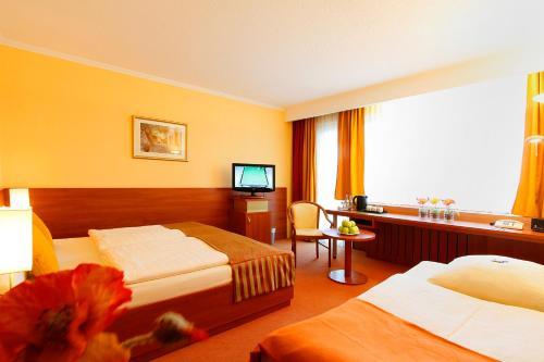 Ein Bett oder Betten in einem Zimmer der Unterkunft Centro Hotel Norderstedter Hof