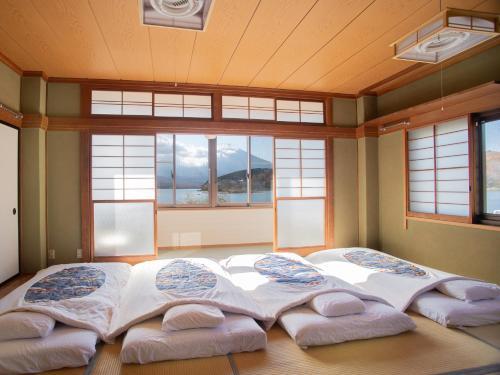 A bed or beds in a room at OYO Ryokan Lakeside Inn Fujinami Yamanakako