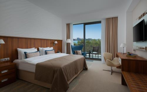A bed or beds in a room at Primorie Grand Resort Hotel 5*