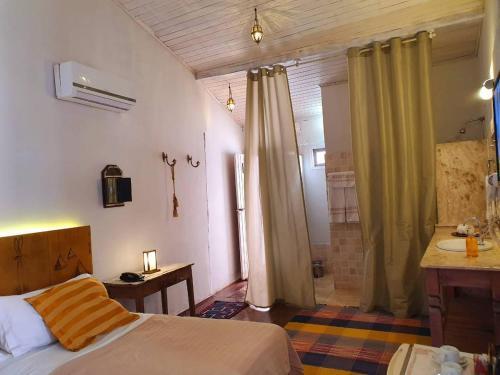 A bed or beds in a room at Solar das Artes Pousada Boutique - Morro