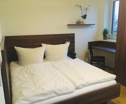 A bed or beds in a room at Pension Seecafé