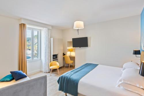 A bed or beds in a room at Best Western Hotel du Roy d'Aragon
