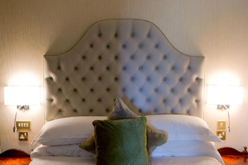 A bed or beds in a room at Fitzpatrick Castle Hotel