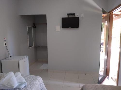 Una televisión o centro de entretenimiento en Suites do Ratinho