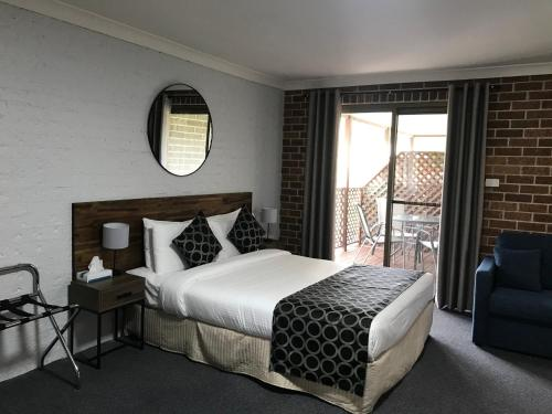 A bed or beds in a room at Coffs Shearwater Motel