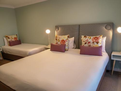 A bed or beds in a room at Nagambie Waterfront Motel