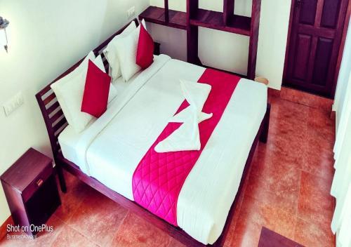 A bed or beds in a room at Cherai Beach Inn