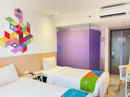 A bed or beds in a room at Dafam Express Jaksa Jakarta