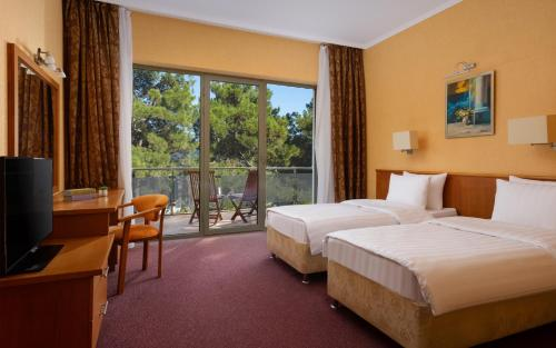 A bed or beds in a room at Primorie Grand Resort Hotel 3*
