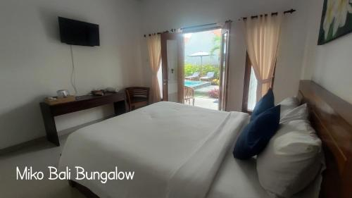 A bed or beds in a room at Miko Bali Bungalow