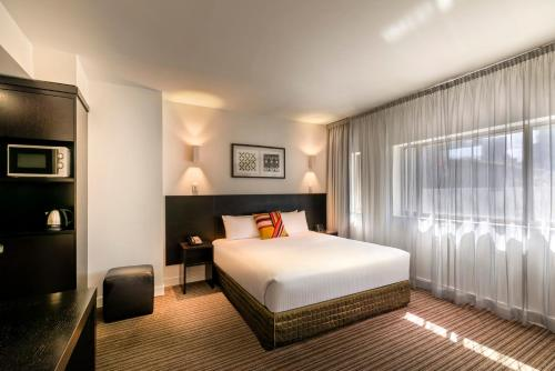 A bed or beds in a room at Causeway 353 Hotel