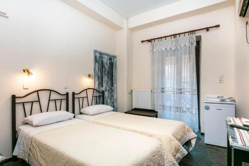 A bed or beds in a room at Acropolis Hotel
