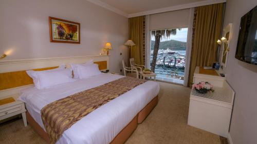 A bed or beds in a room at Ece Saray Marina Resort