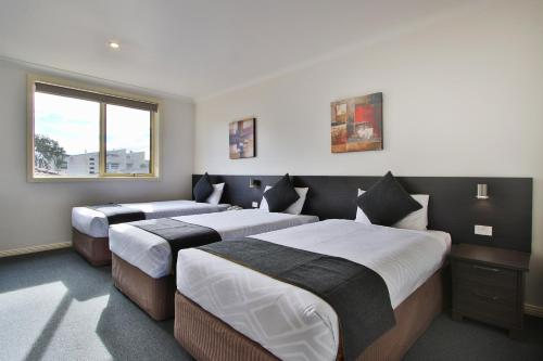 A bed or beds in a room at Comfort Hotel Dandenong
