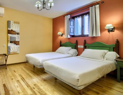 A bed or beds in a room at Hostal Almadiero