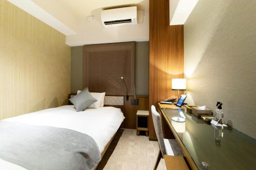 A bed or beds in a room at HOTEL HILLARYS Shinsaibashi