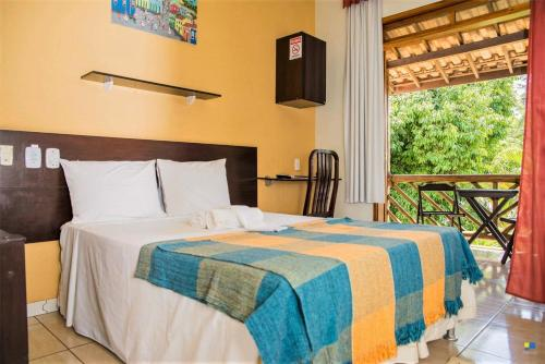 A bed or beds in a room at Pousada Tropicalia