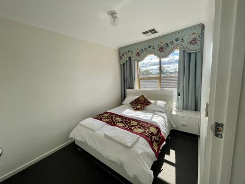 A bed or beds in a room at West Lakes Townhouse