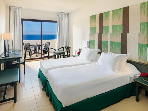 A bed or beds in a room at H10 Taburiente Playa