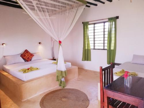 A bed or beds in a room at Red Monkey Beach Lodge