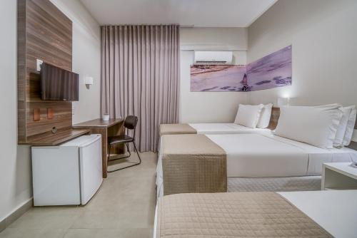 A bed or beds in a room at Tambaqui Praia Hotel