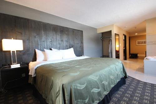 A bed or beds in a room at Quality Inn Bracebridge