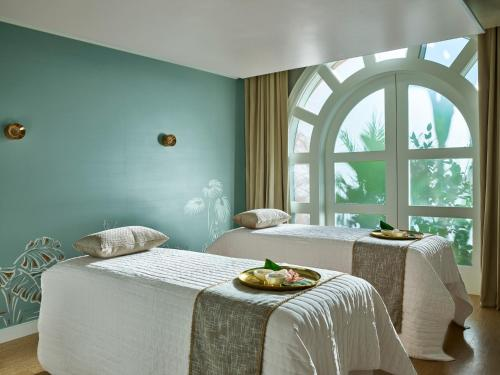 A bed or beds in a room at The Beverly Hills Hotel - Dorchester Collection