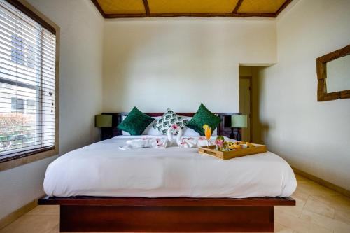A bed or beds in a room at The Placencia, a Muy'Ono Resort
