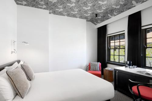 A bed or beds in a room at Peppers Gallery Hotel