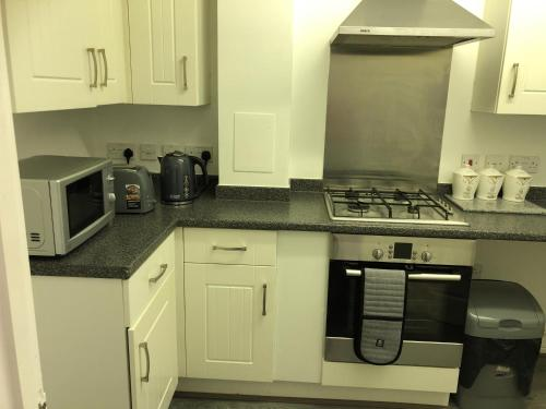 A kitchen or kitchenette at MODERN 2 BED HOUSE WITH GARDEN AND PARKING