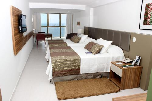 A bed or beds in a room at Nobile Suítes Executive