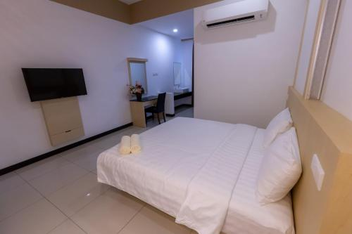 A bed or beds in a room at Scott Service Suites Sdn Bhd