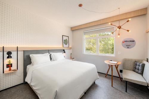 A bed or beds in a room at Intercity Porto Alegre Aeroporto