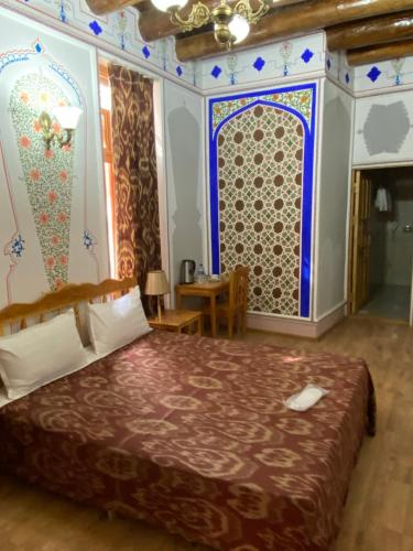 A bed or beds in a room at Komil Bukhara Boutique Hotel